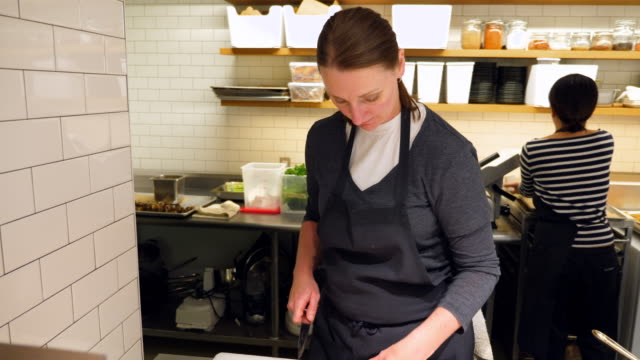 PAN Female chef preparing salmon for dinner service in restaurant kitchen