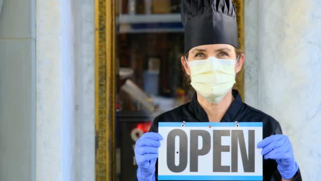 stockvideo's en b-roll-footage met het vrouwelijke chef-kokrestauranteigenaar dat het stellen van een masker dat een open teken houdt - bord open