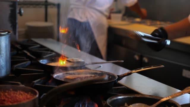 cu female chef working at stove in restaurant kitchen - コントロール点の映像素材/bロール