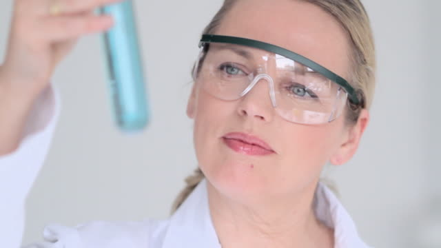 cu female chemical researcher studying glass flask of blue chemical / new york city, usa - safety glasses stock videos & royalty-free footage