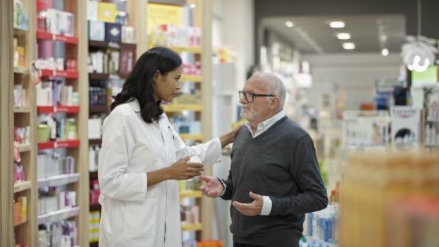 chemikerin erklärt medikamenten an älteren mann - apothekerberuf stock-videos und b-roll-filmmaterial