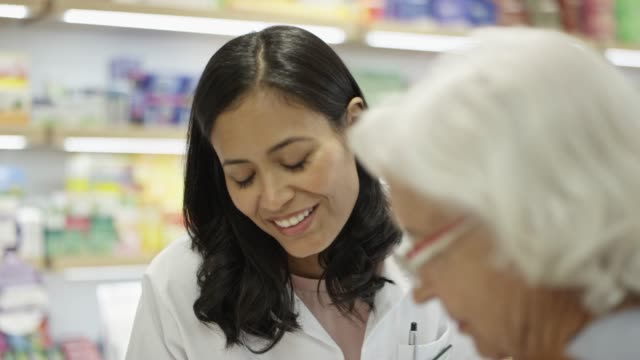 female chemist talking to elderly woman in pharmacy - selective focus stock videos & royalty-free footage