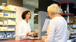 Female chemist with receipt talking with customer
