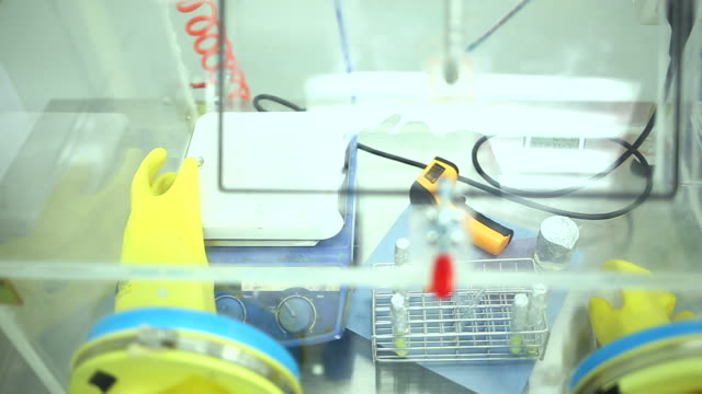 female chemist works in isolation glove box - glove box stock videos & royalty-free footage