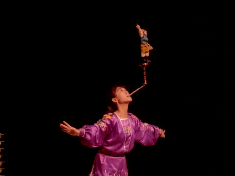 female circus artists balances toy in air using her mouth, china - effigy stock videos & royalty-free footage