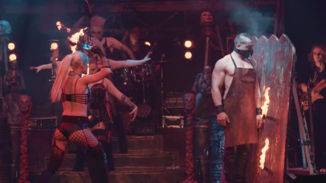 female circus performer throws flaming knives into a board beside her strong man co-star - musical burlesco video stock e b–roll