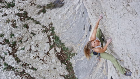 vidéos et rushes de grimpeur femelle ascendant de la falaise - risque