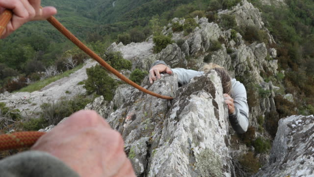 female climber ascends rock ridge above valley, mountains - corda video stock e b–roll