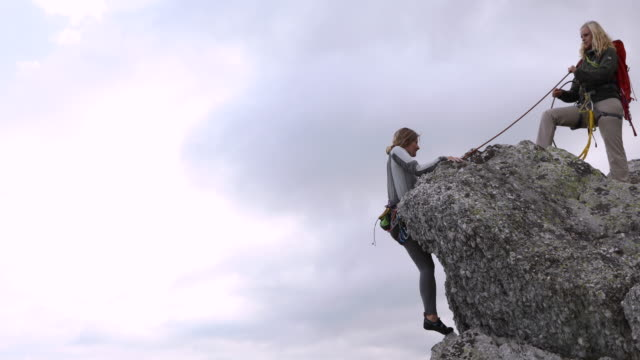 female climber ascends rock ridge above valley, mountains - imbracatura di sicurezza video stock e b–roll