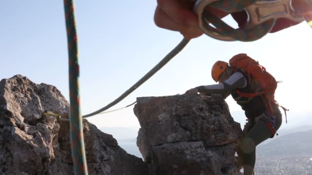 female climber ascends to pinnacle summit at sunrise - belaying stock videos & royalty-free footage