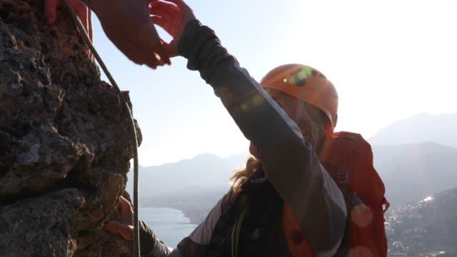 klettersteigerin steigt bei sonnenaufgang auf den gipfel - fels stock-videos und b-roll-filmmaterial