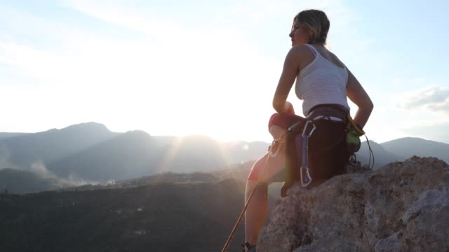 female climber ascends to pinnacle summit, at sunrise - krab stock videos & royalty-free footage