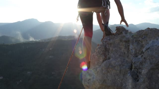 female climber ascends to pinnacle summit, at sunrise - trovare video stock e b–roll