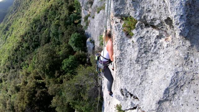 female climber ascends vertical rock wall - superare le avversità video stock e b–roll
