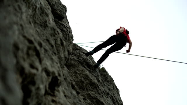 female climber belaying from the cliff - belaying stock videos & royalty-free footage