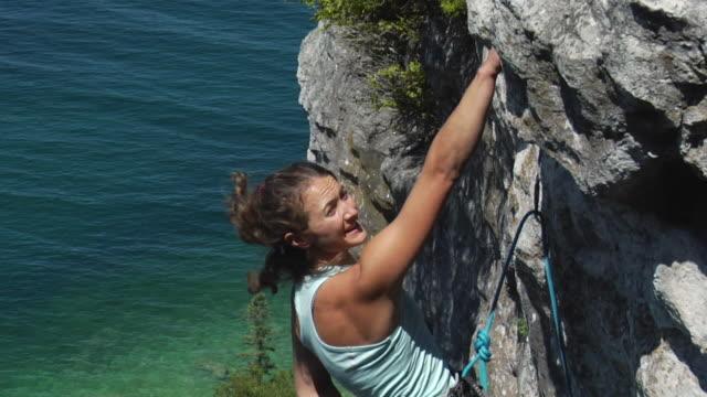 vídeos de stock, filmes e b-roll de ms female climber climbing cliff, lion's head, ontario, canada - corda de escalada