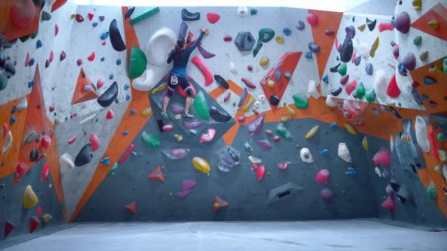 stockvideo's en b-roll-footage met slo mo ld vrouwelijke klimmer die de binnenklimmende kei beklimt - boulder