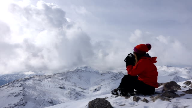 female climber drinks coffee in the summit