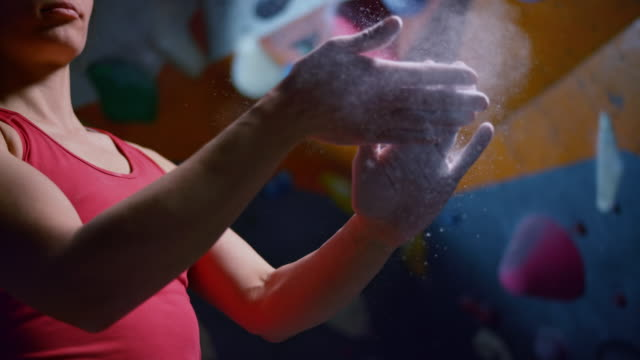 SLO MO LD Female climber dusting her hands in the indoor climbing gym
