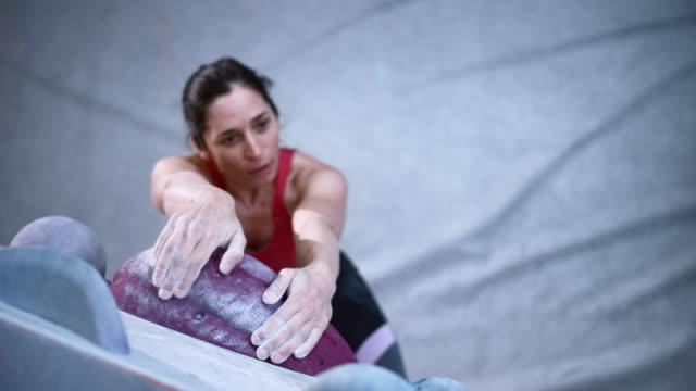 stockvideo's en b-roll-footage met slo mo vrouwelijke klimmer die een greep op een muur in een overdekt het beklimmen gymnastiek vindt - free climbing