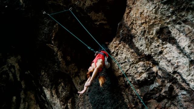 stockvideo's en b-roll-footage met vrouwelijke klimmer die van de rots hangt - vrij klimmen