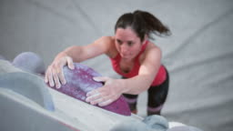 SLO MO LD Female climber hanging on a hold in an indoor bouldering gym