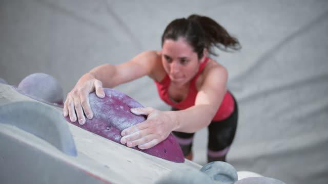 vídeos y material grabado en eventos de stock de slo mo ld escalador femenino colgado de una bodega en un gimnasio de boulder interior - coraje