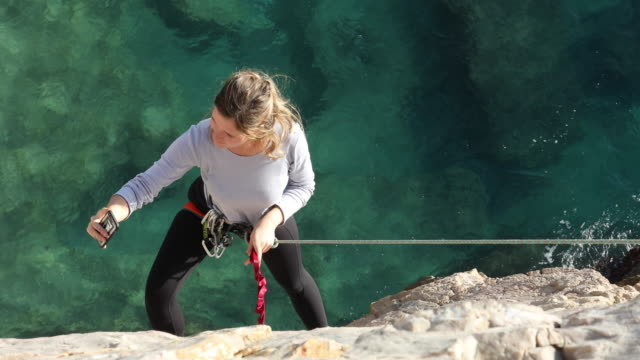 female climber hangs off end of rope while shooting selfies - danger stock videos & royalty-free footage