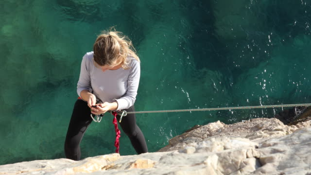 female climber hangs off end of rope while shooting selfies - climbing rope stock videos & royalty-free footage