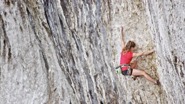 female climber in red shirt ascending a cliff - climbing stock videos & royalty-free footage