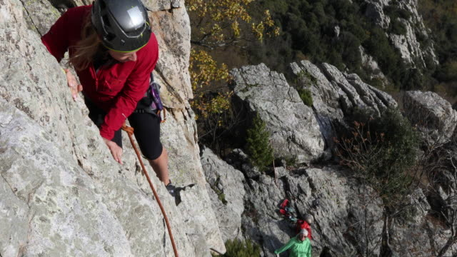 female climber makes difficult moves on rock cliff - pedal pushers stock videos & royalty-free footage