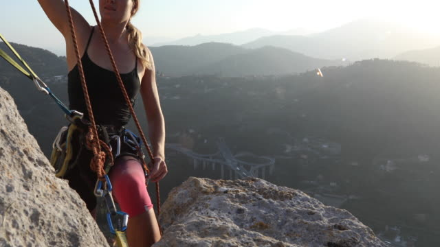 female climber organizes rope and gear on cliff edge, at sunrise - camisole stock videos & royalty-free footage
