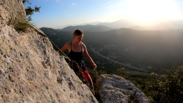 klettererin organisiert seil und ausrüstung am klippenrand, bei sonnenaufgang - kamisol stock-videos und b-roll-filmmaterial