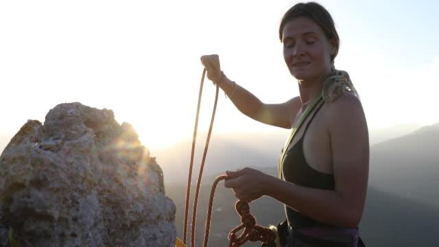 klettererin organisiert seil und ausrüstung auf gipfel, bei sonnenaufgang - kamisol stock-videos und b-roll-filmmaterial