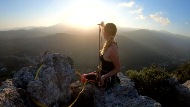 vídeos y material grabado en eventos de stock de la escaladora femenina organiza cuerda y equipo en la cumbre, al amanecer - camisola