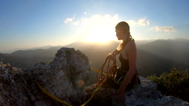 female climber organizes rope and gear on summit, at sunrise - skill stock videos & royalty-free footage
