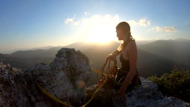 女性登山者在日出時在山頂組織繩索和裝備 - 技能 個影片檔及 b 捲影像