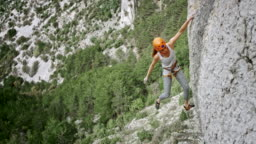 Female climber positioning the quickdraw and clipping the rope