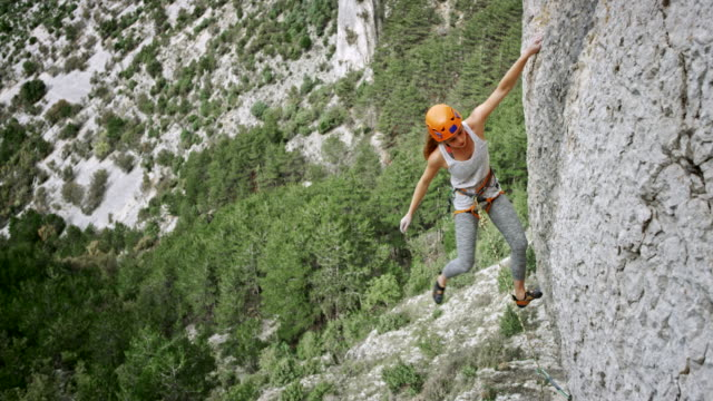 female climber positioning the quickdraw and clipping the rope - cliff stock videos & royalty-free footage