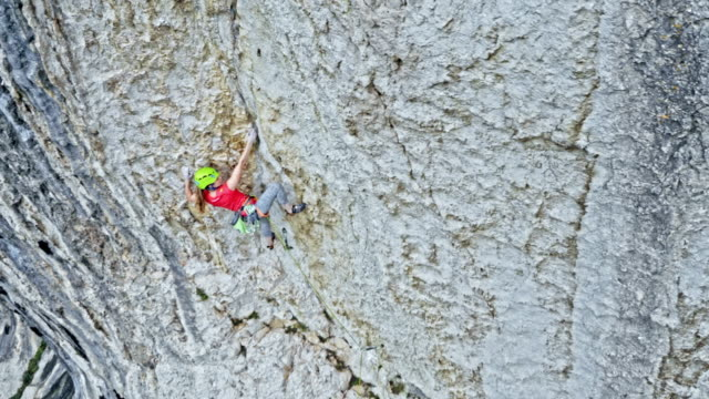 aerial female climber pulling her rope through the quickdraw while standing in the cliff - climbing rope stock videos & royalty-free footage