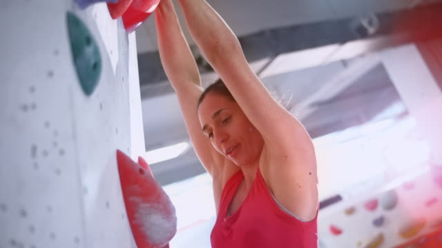 slo mo ts female climber reaching the top of the indoor climbing wall - free climbing stock videos & royalty-free footage