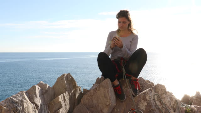Female climber relaxes on rock summit above sea
