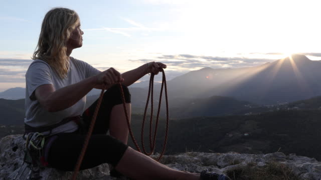 female climber relaxes on rock summit, at sunrise - rope stock videos & royalty-free footage