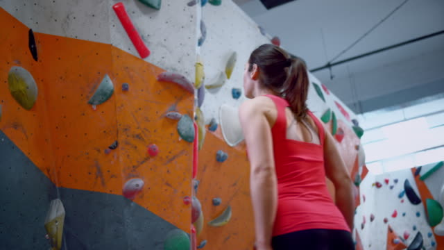 slo mo female climber standing beneath an indoor climbing wall and reading the route - free climbing stock videos & royalty-free footage