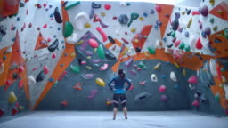SLO MO LD Female climber standing in an indoor climbing gym looking at the climbing wall