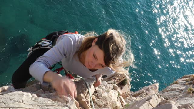 垂直の岩崖を登るに苦労する女性登山家 - 自分撮り点の映像素材/bロール