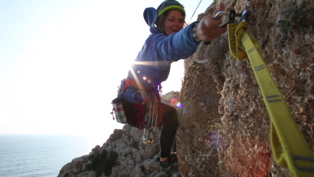 female climber swings on end of rope to clip anchor - helmet stock videos & royalty-free footage