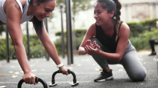 vídeos y material grabado en eventos de stock de female coach and woman doing fitness together. - entrenamiento sin material