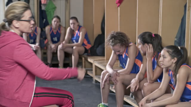 Female coach smiling and telling joke to young players in locker room