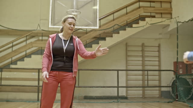 Female coach supporting young team while training on court